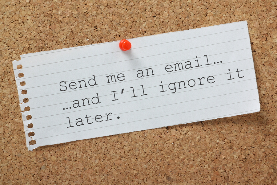 The phrase Send me an email and I'll Ignore it Later on a cork notice board. A concept for time wasting or avoiding being overwhelmed by communications and workload